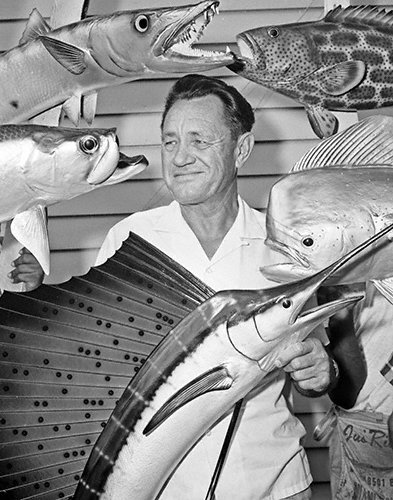 CELEBRITIES (2-251LR) Al Pfleuger taxidermist surrounded by his mounts in shop.jpg