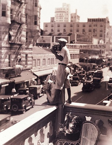 Charles C. Ebbets (3-03LR) standing on balcony over city w camera. c. 1923.jpg