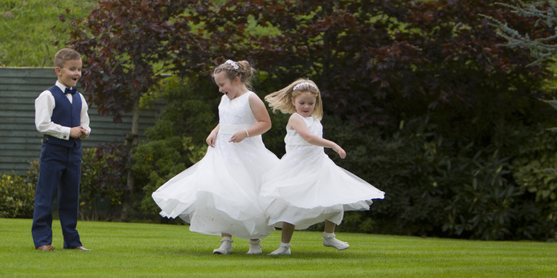 Flower-Girls-Dancing-Carrickdale-Garden.jpg :: Here at Andrew Mackin Photography, our aim is to make your wedding day as relaxing & memorable as possible. We'll get to know you before your big day to find out your likes, needs & wants. We know that every couple & wedding are different, therefore we strive to personalise & customise every part of your day, from morning preparations, to the cutting of the cake & beyond if required.