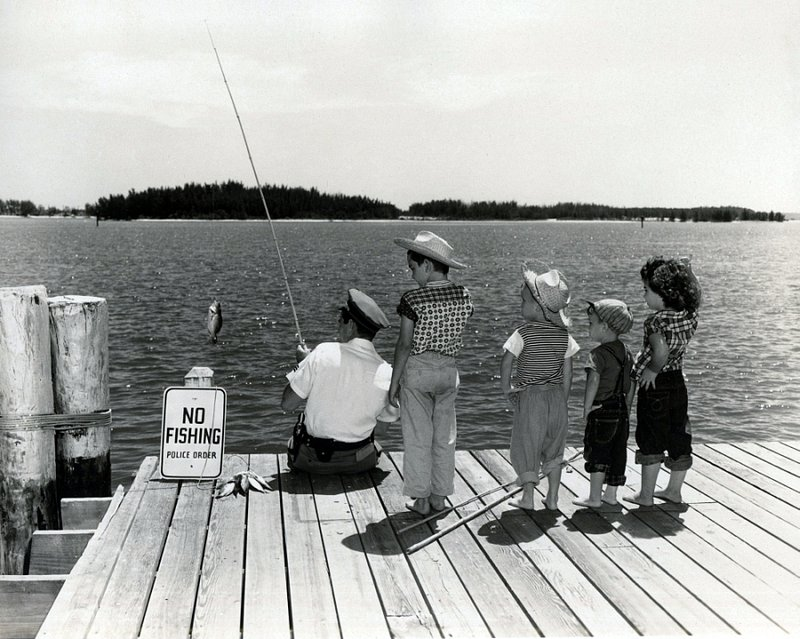 SCELLANEOUS 9-56 police officer fishing by no fishing sign as children watch c. 1957.1.jpg
