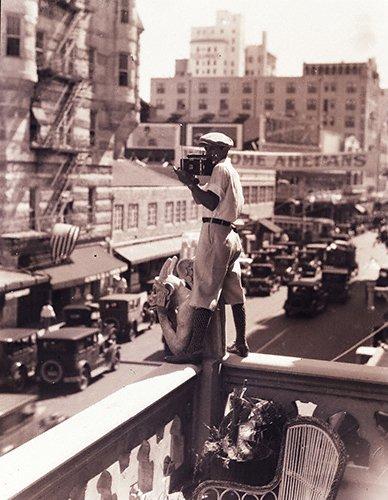 Charles C. Ebbets (3-03LR) standing on balcony over city w camera. c. 1923.jpg