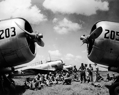 ON 1-83  pilots sitting on Florida airfield framed by nosecones of airplanes 19421.jpg