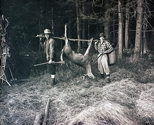 SPORTS HUNTING 16-031 carrying deer in woods w friend c. 1926 ORIG. GLASS NEG.SCAN.jpg