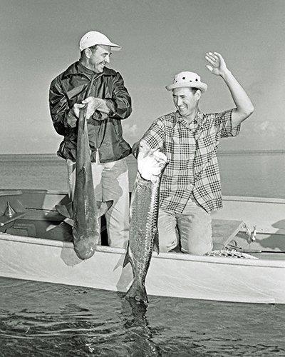 celebrities (2-052LR) Ted Williams w Sam Snead-TW raising his hand in mockery of SS shark catch.jpg
