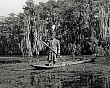 SEMINOLES (13-010LR)  man in full tribal regalia. poling dugout canoe in FLorida Everglades.jpg