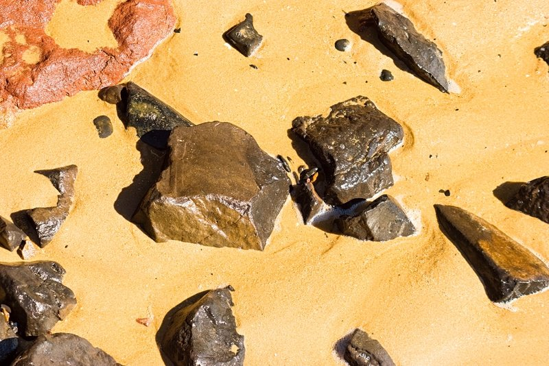Rocks in the Sand.jpg :: Wet rocks of various colours in a sandy beach