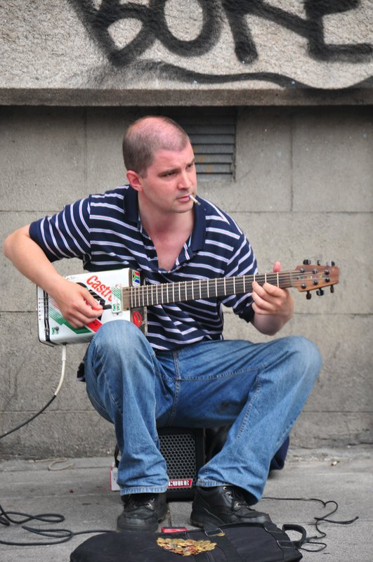 Street Minstral.jpg :: Wherever I travel I always find street minstrels this young Dublin wannabe plays a homemade guitar of which the base is made from an old petroleum can.