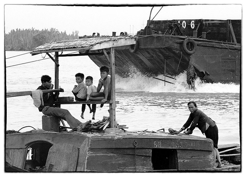 Boat People.jpg :: In the Delta region many Vietnamese live and make their livelihood on boats. During the war they shared the waters with the US Military., often times causing concern for the safety and well being of US ships and personnel.